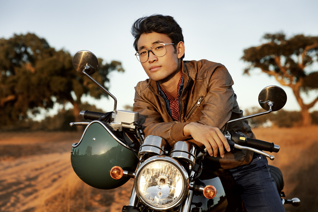 Man sat on motorcylce wearing spectacles
