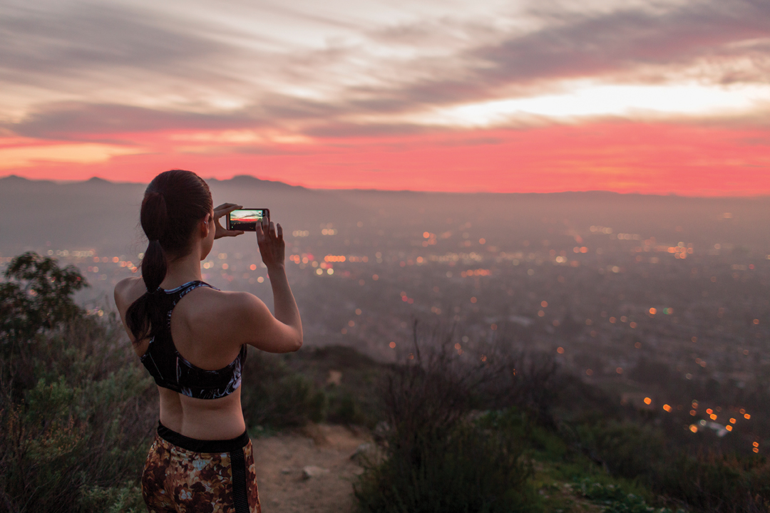 Woman in jogging attire taking picture of a sunset