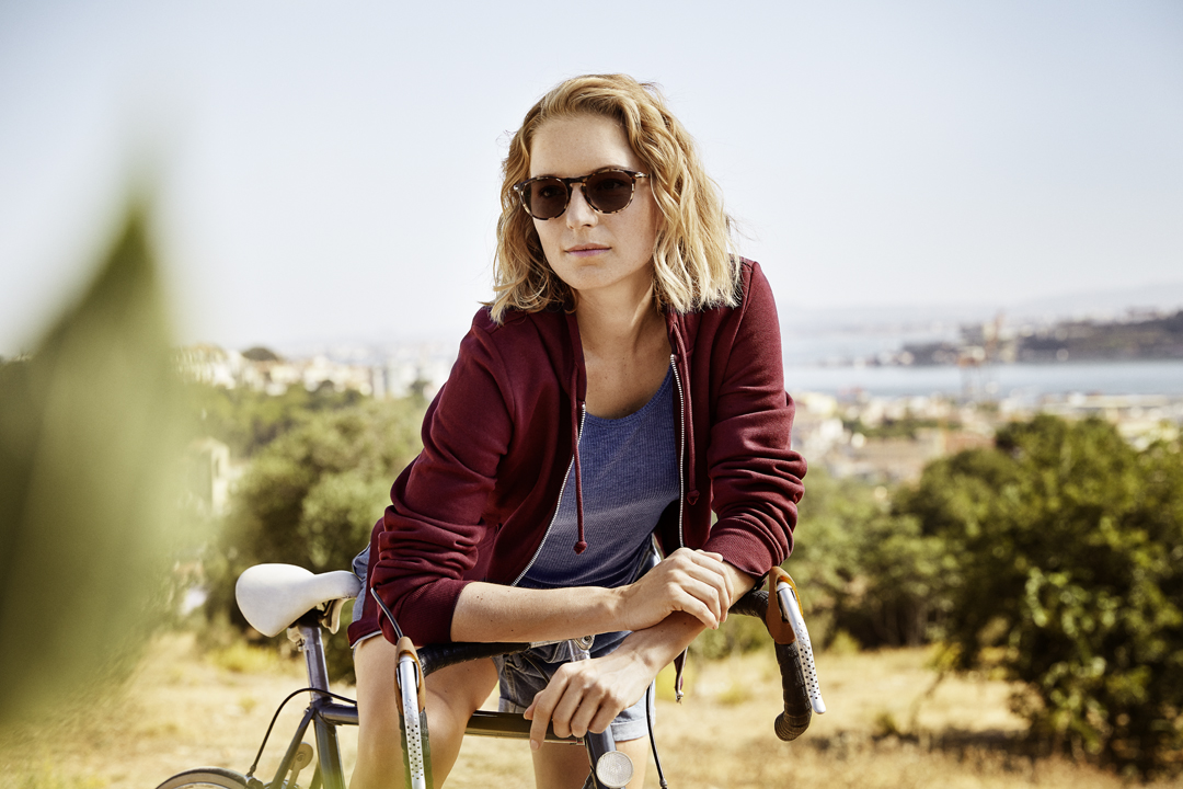 Lady wearing Essilor lenses with Transitions Signature sat on bicycle
