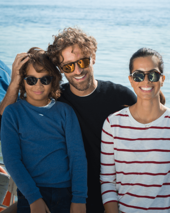 Family wearing Essilor lenses with Xperio Polarised by the sea