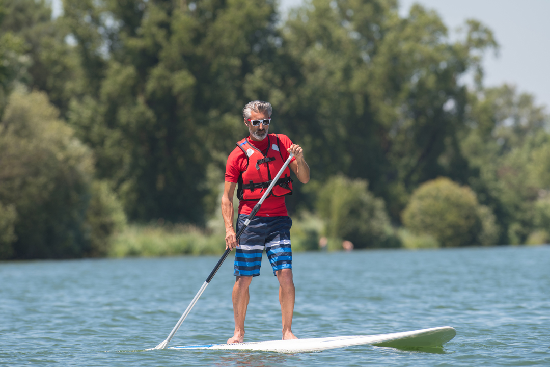 Man paddleboarding wearing polarised sunglasses