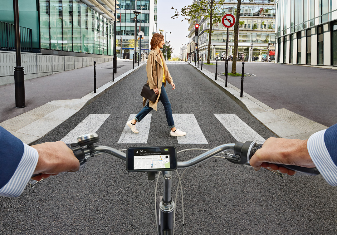 Man cycling on road and woman crossing on zebra crossing