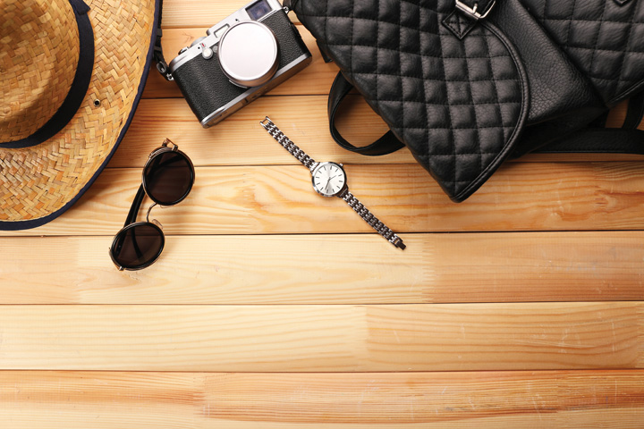 Layout of sunglasses, sunhat, camera, watch and handbag
