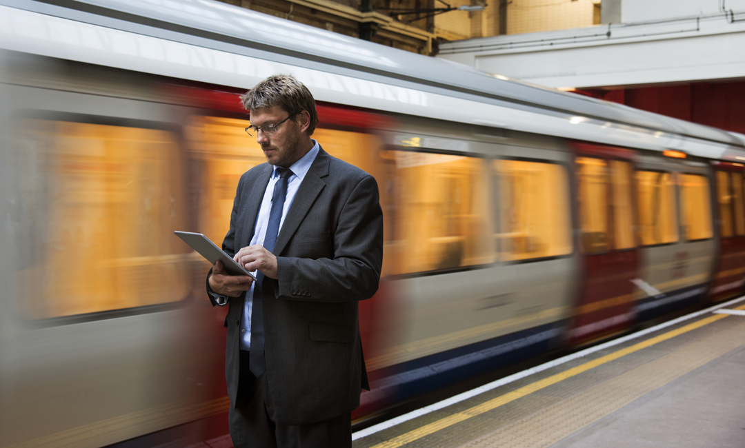 Man looking at tablet with train passing behind