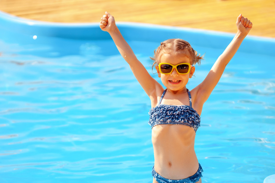 Little girl wearing sunglasses with arms in the air stood in front of a swimming pool