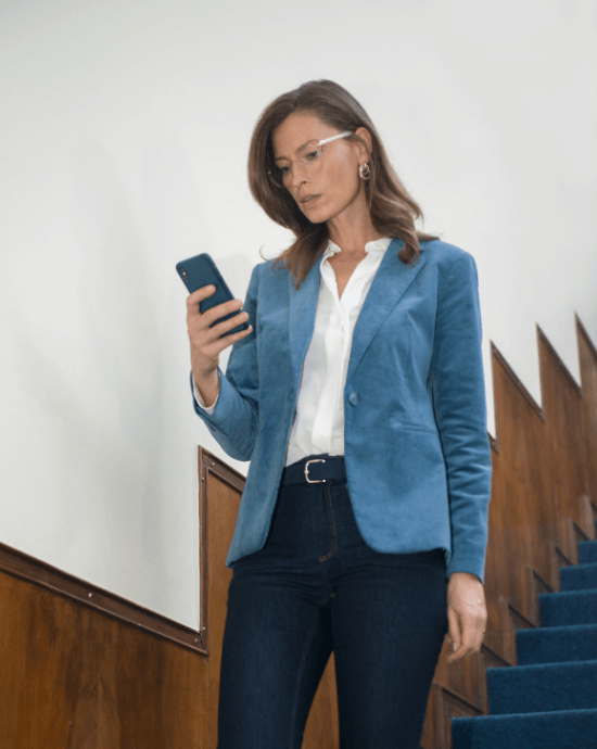 Lady wearing Varilux X series and focusing on her smart phone