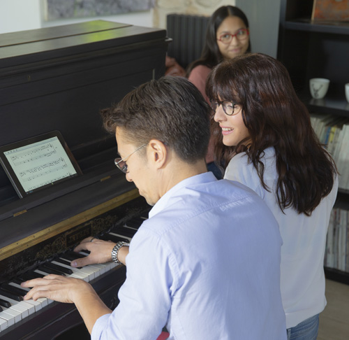 Couple wearing glasses playing the piano