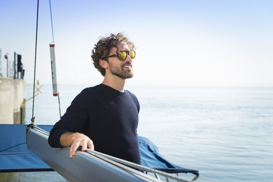 Man wearing polarised lenses stood on a boat holding the rigging