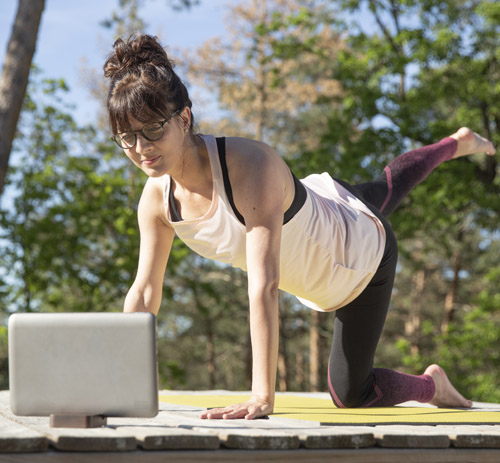 Woman wearing Varilux Comfort Max doing yoga and looking at tablet