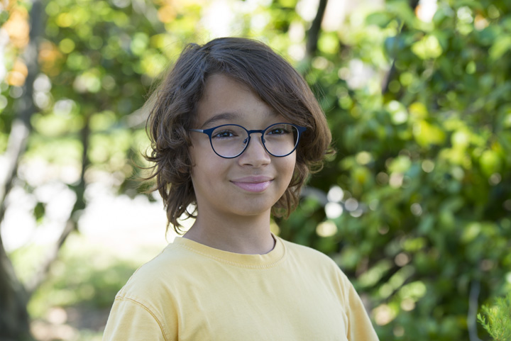 Boy wearing glasses with Essilor lenses enhanced by Crizal Sapphire UV
