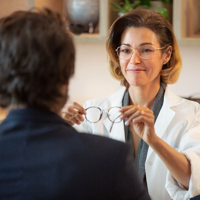 Dispensing optician delivering new pair of  glasses to her patient