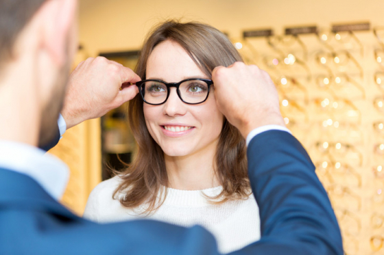 Optician fitting glasses to patient