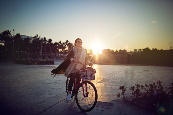 Woman wearing polarised lenses on a bicycle with a sunset in the background