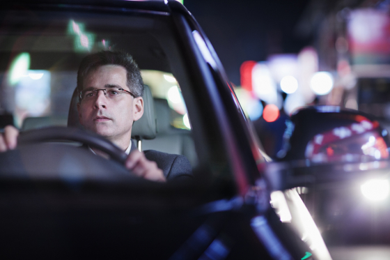 Man wearing spectacles driving in a car