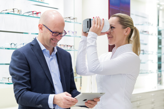 A woman tries Essilor lenses in an opticians using a virtual reality headset