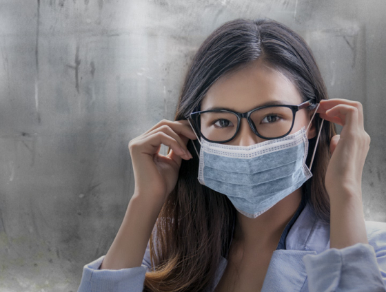 Woman wearing face mask and clear glasses lenses thanks to Optifog lens coating