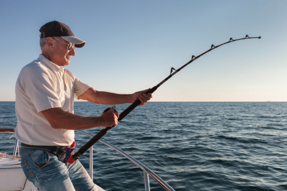 Man wearing sunglasses fishing on a boat