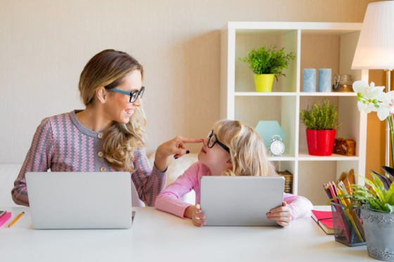 Mother and daughter sat at table using laptops