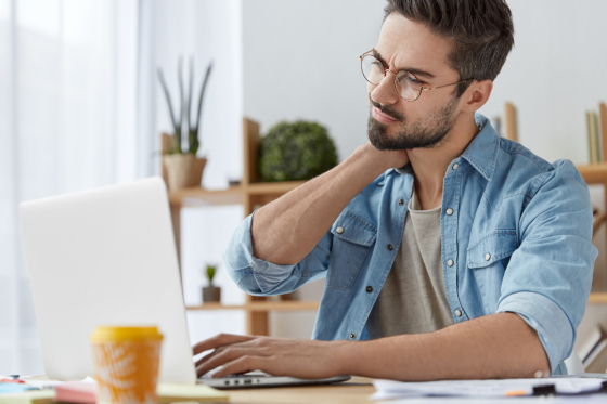Man wearing spectacles looking at laptop holding his neck in pain