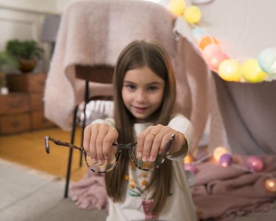 Little girl holding lenses of spectacles