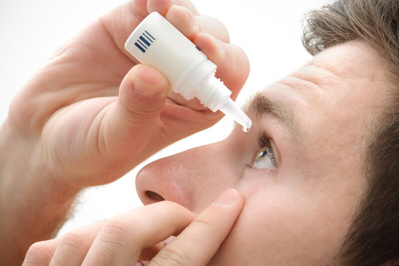 a man dropping eye drops in to his eye