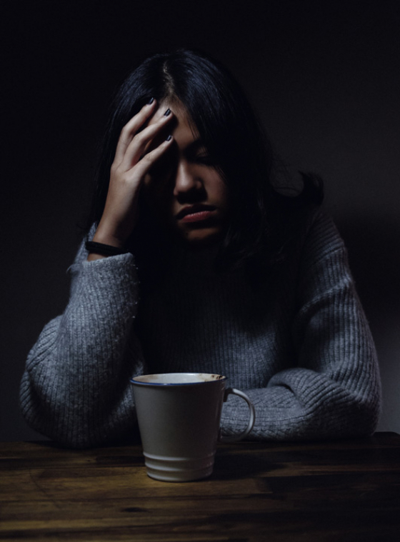 A woman sitting with a coffee experiencing an ocular migraine