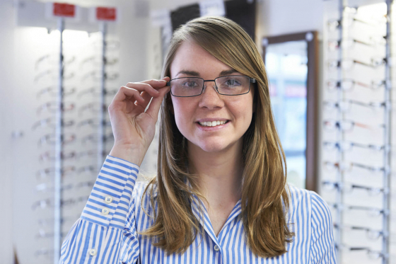 lady putting on her glasses in an optician to correct long-sightedness