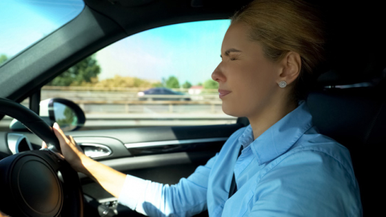 Woman driving closes her eyes to relief eye fatigue caused by staring at same distance