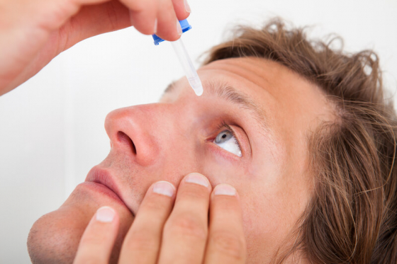 man putting eyedrops in his eye to manage glaucoma