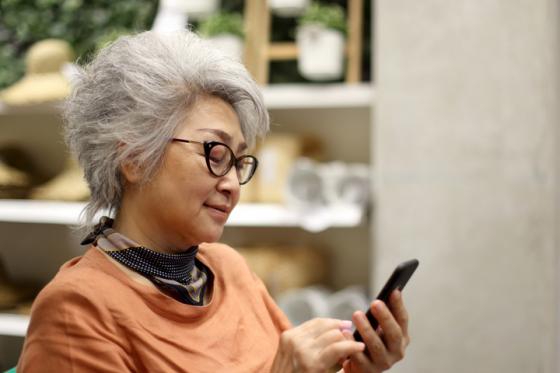 Woman wearing varifocal lenses surfs the web on her phone