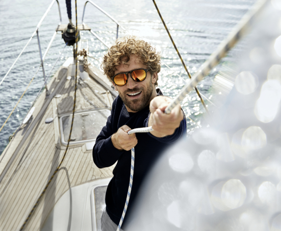 Man wearing sunglasses pulls at the rigging on a boat