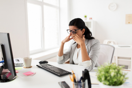 Woman sat at desk lifts up spectacles to rub tired eyes