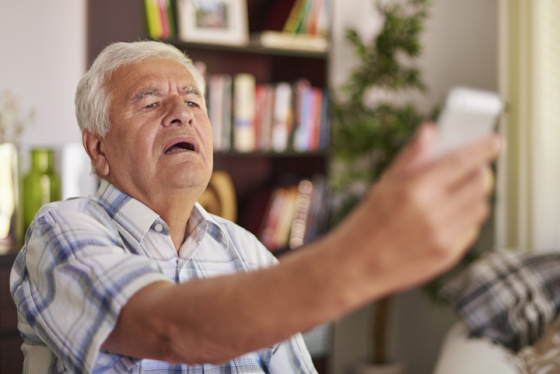 A man struggles to see his phone due to presbyopia so stretches his arm out to see more clearly