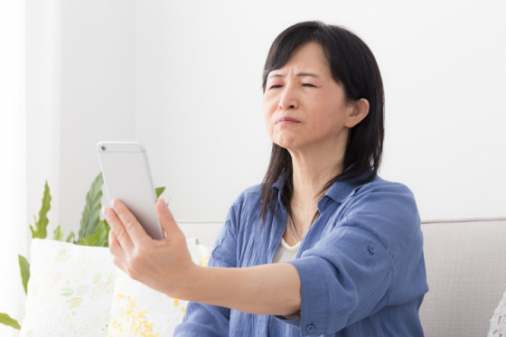 Woman struggling to read text on phone due to presbyopia