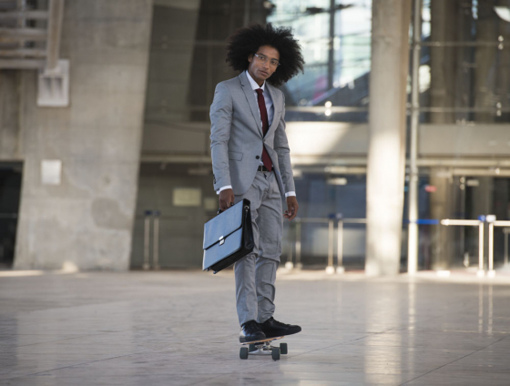 Gentleman wearing spectacles on skateboard