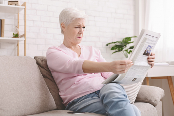 Woman struggling to see newspaper text due to presbyopia