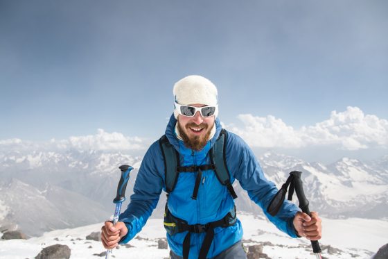 Man hiking up mountain wearing a beanie and sunglasses