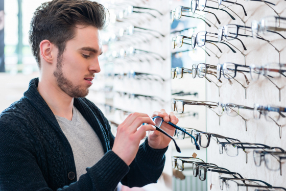 Man looking at rows of spectacle frames