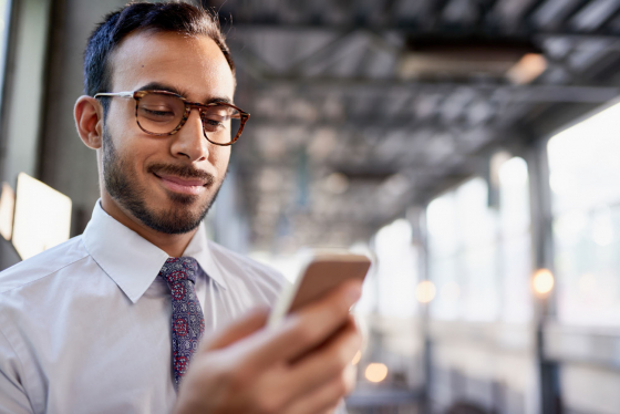 Man wearing spectacles, smiling, looks at smartphone