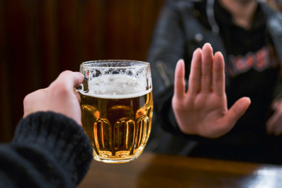 A person refusing a pint of beer while taking part in dry January