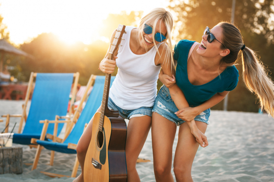 Two ladies on the beach with a guitar