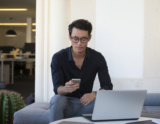 Man holding smartphone looking at laptop screen