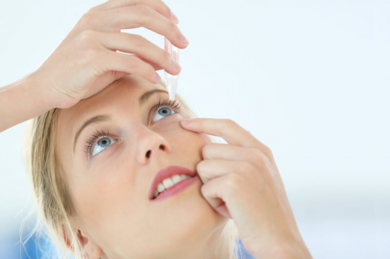 woman placing eye drops in her eye