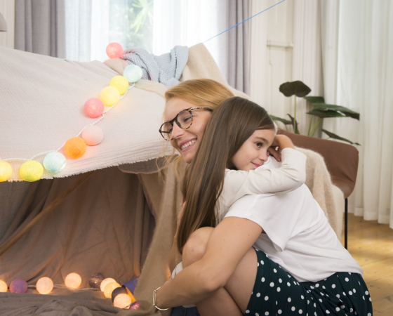 Little girl hugging mother who is wearing spectacles