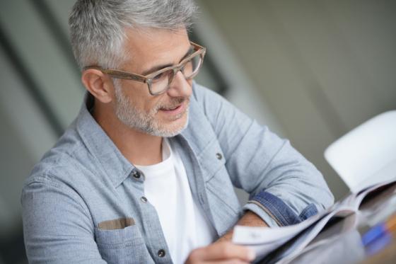 Man wearing varifocal lenses smiling when reading his newspaper