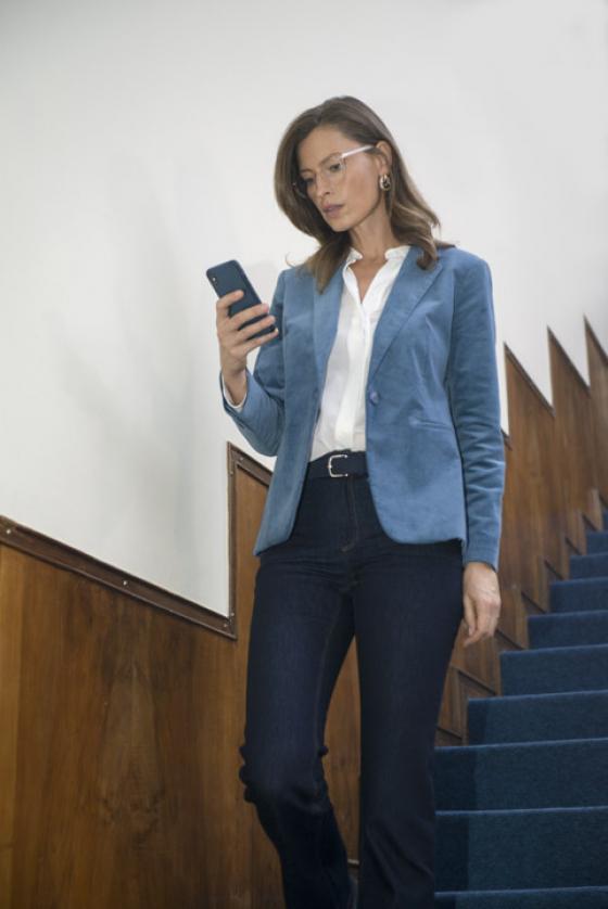 Woman walking downstairs wearing varifocal lenses looking at phone