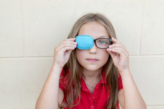 Little girl wearing glasses with an eye patch to correct strabismus