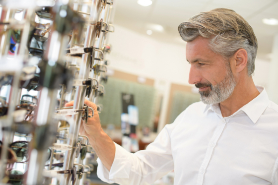 Man choosing glasses from rack in opticians