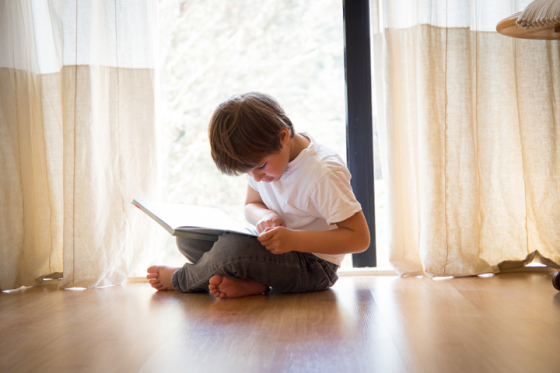 Little boy sat on floor struggling to read book due to astigmatism