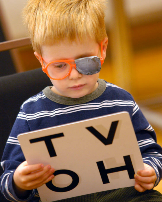 Child having his eyes tested with a patch on his glasses